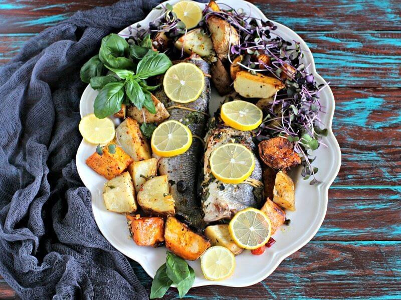 This oven roasted whole branzino recipe makes for an easy and fabulous dinner of tender, juicy fish on a bed of white and sweet roasted potatoes.