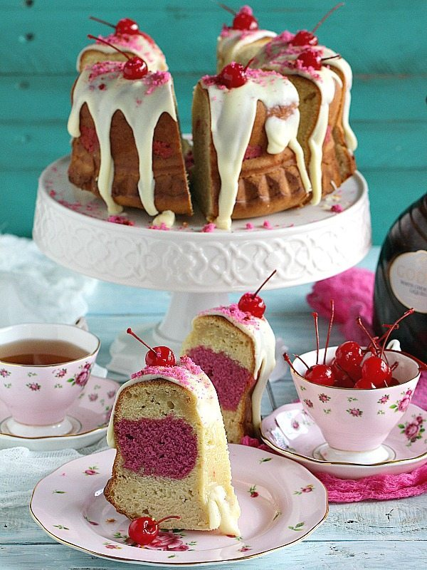 Cherry and almond flavors are combined in a soft and velvety Ricotta Bundt Cake topped with white chocolate icing and maraschino sweet cherries.