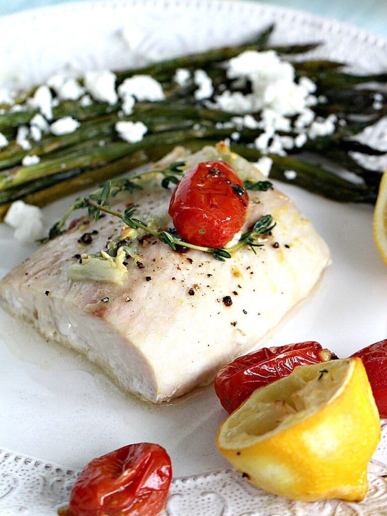 Oven roasted mahi mahi fillet with grape tomatoes, lemon, and a side of roasted asparagus with feta cheese