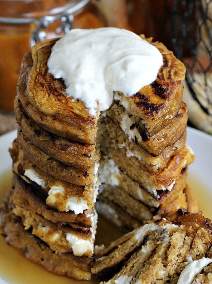 Pumpkin cheesecake pancakes topped with cream on a white plate