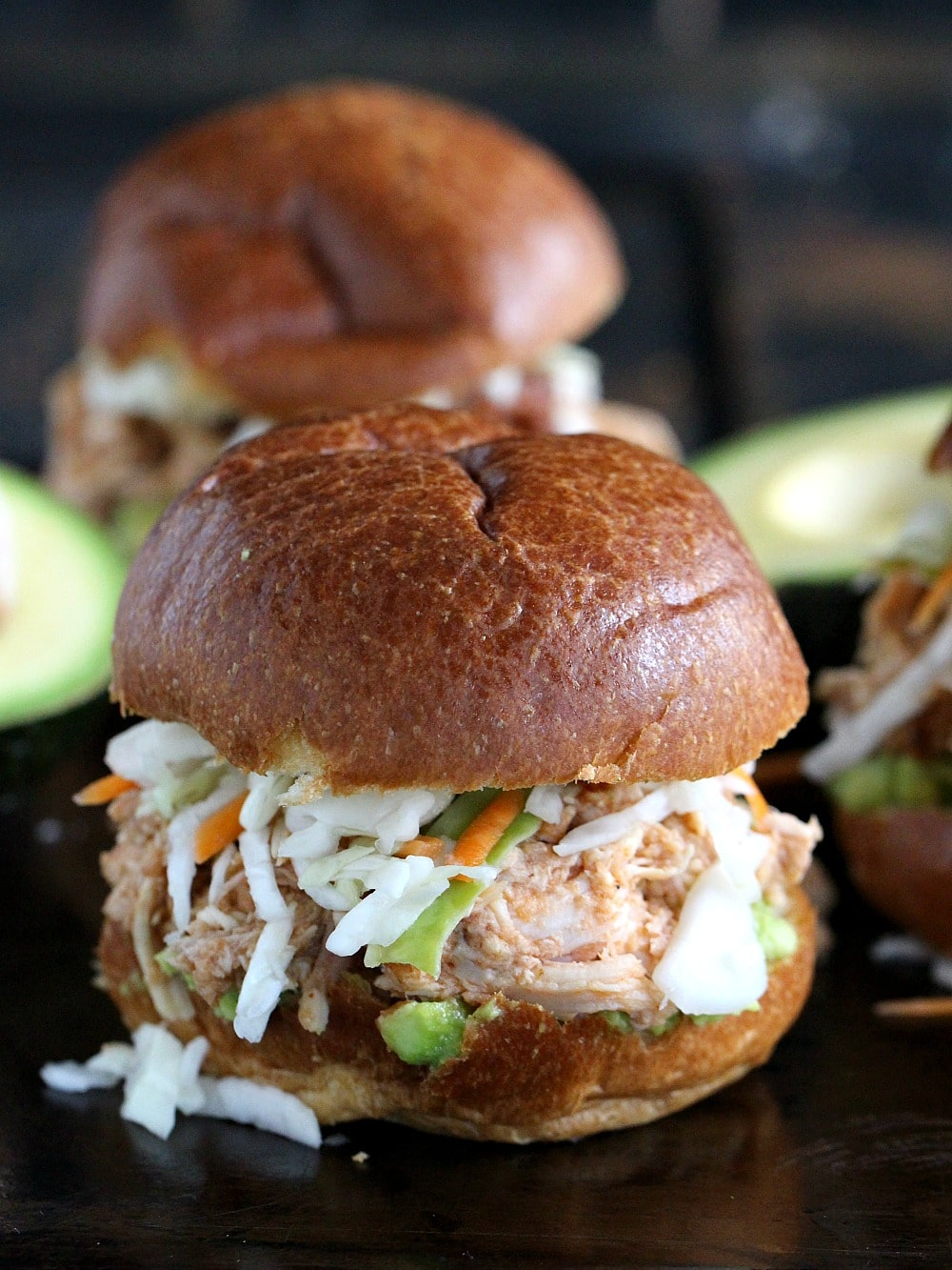 No Cook Spicy Chicken Sliders are made with rotisserie chicken, guacamole, cole slaw and spicy Veracha sauce for an easy and delicious appetizer or entree.
