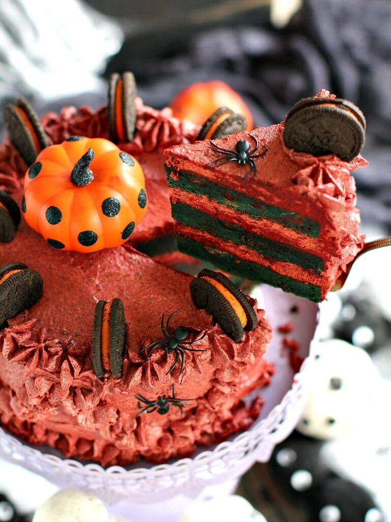 Delicious and decadent Pumpkin Oreo Cake with pumpkin chocolate chip layers and Oreo buttercream is dressed up and garnished for Halloween.