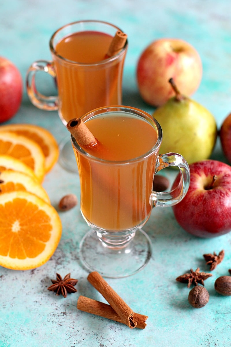 Apple cider garnished with star anise and whole cinnamon sticks in individual glass cups