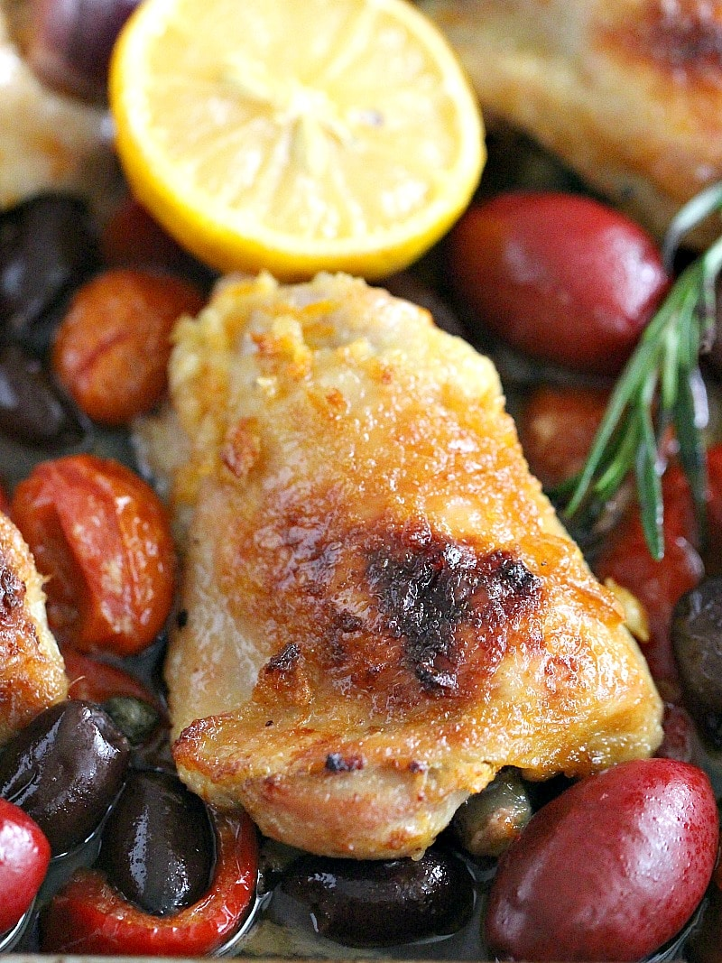 One Sheet Pan Mediterranean Chicken with olives, capers, red onion, red pepper and grape tomatoes in a fresh lemon orange honey sauce. A hearty, easy meal!