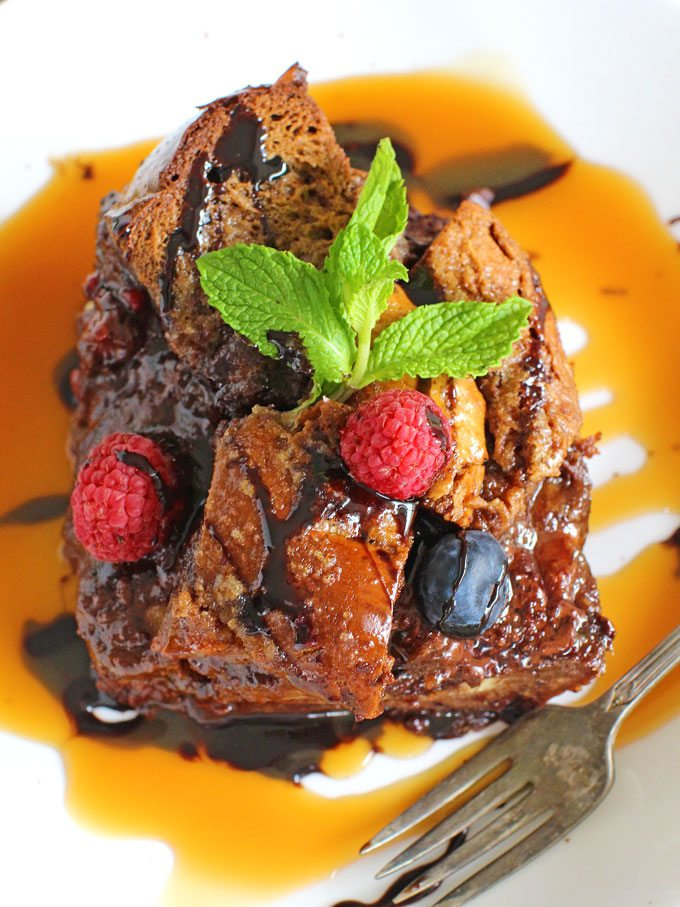 Chocolate Challah French Toast Casserole served with caramel sauce and fresh fruits.