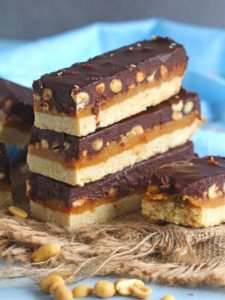 Homemade Snickers Bars are very easy to make and melt in your mouth with deliciousness. Buttery shortbread, caramel with crunchy peanuts and lots of chocolate!