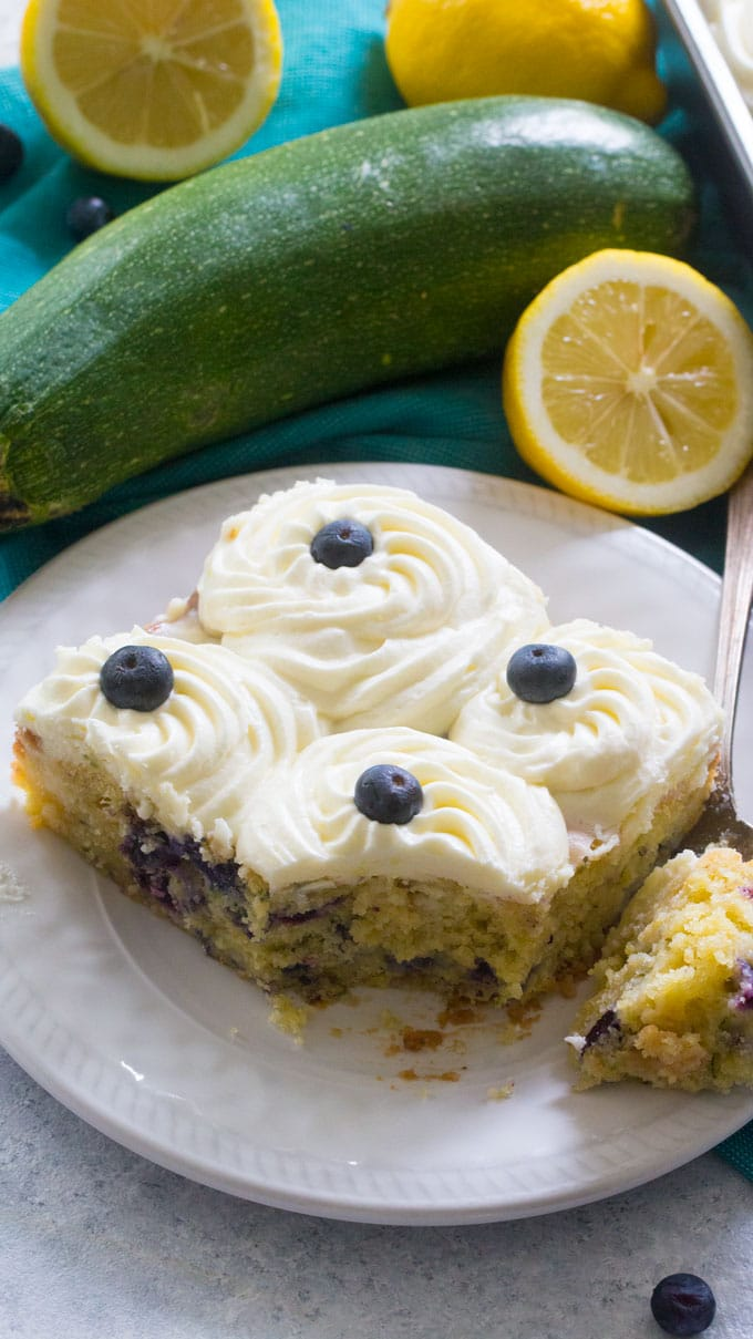 Blueberry Zucchini Poke Cake is so tender, moist and delicious. Made with zucchini, olive oil, lots of fresh lemon zest and juicy blueberries. Topped with lemon buttercream!