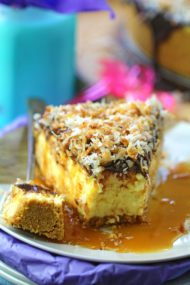 The best and creamiest No Bake Coconut Cheesecake is indulgent and delicious. Topped with chocolate ganache, lots of toasted coconut and finished with caramel sauce.