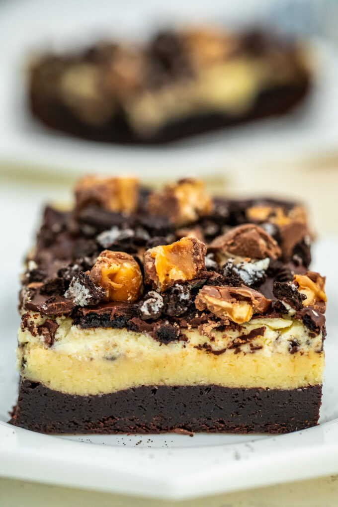 Photo of chocolate oreo brownies bars topped with chopped snickers.