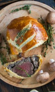 Best Beef Wellington cooked perfectly while wrapped in puff pastry, ham and the most amazing mushroom duxelles made with cognac duck liver mousse pate.