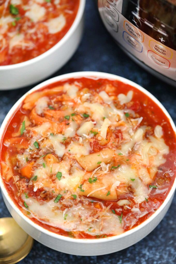 Image of homemade lasagna soup garnished with shredded cheese in a white bowl.