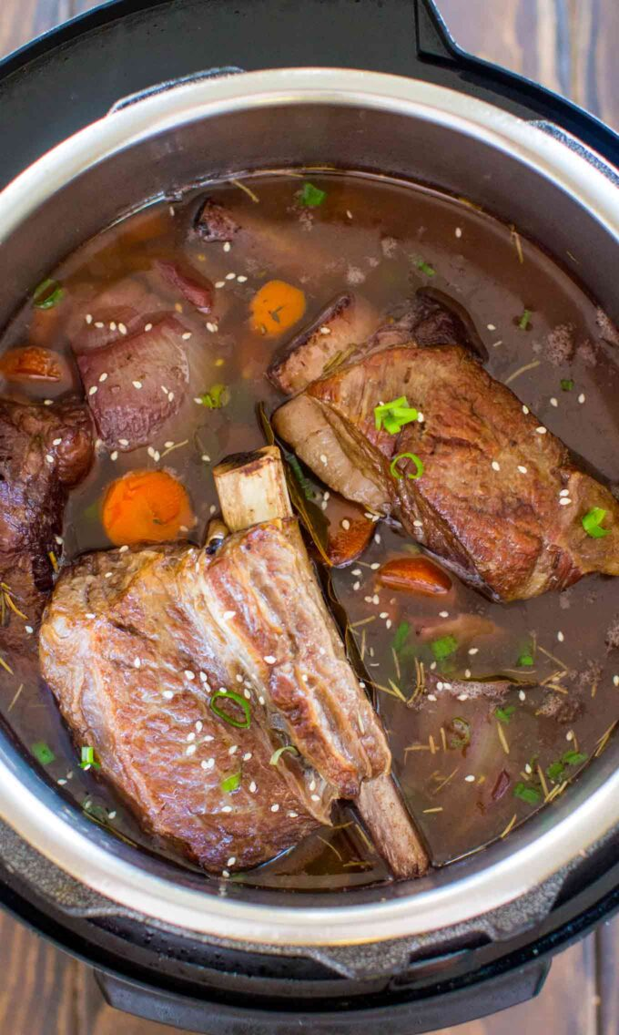 Image of pressure cooker short ribs with carrots and sesame seeds.