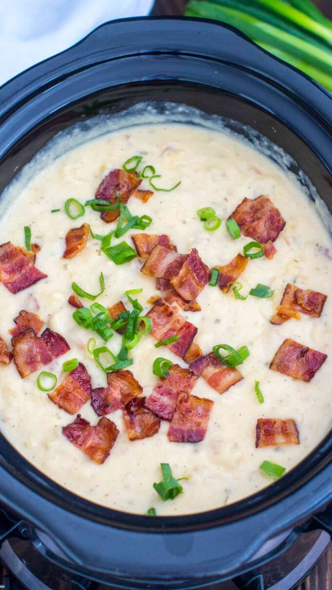 picture of slow cooker baked potato soup garnished with bacon and chopped green onion