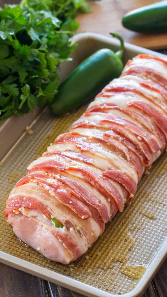 Image of pork tenderloin wrapped in bacon on a cooking tray.