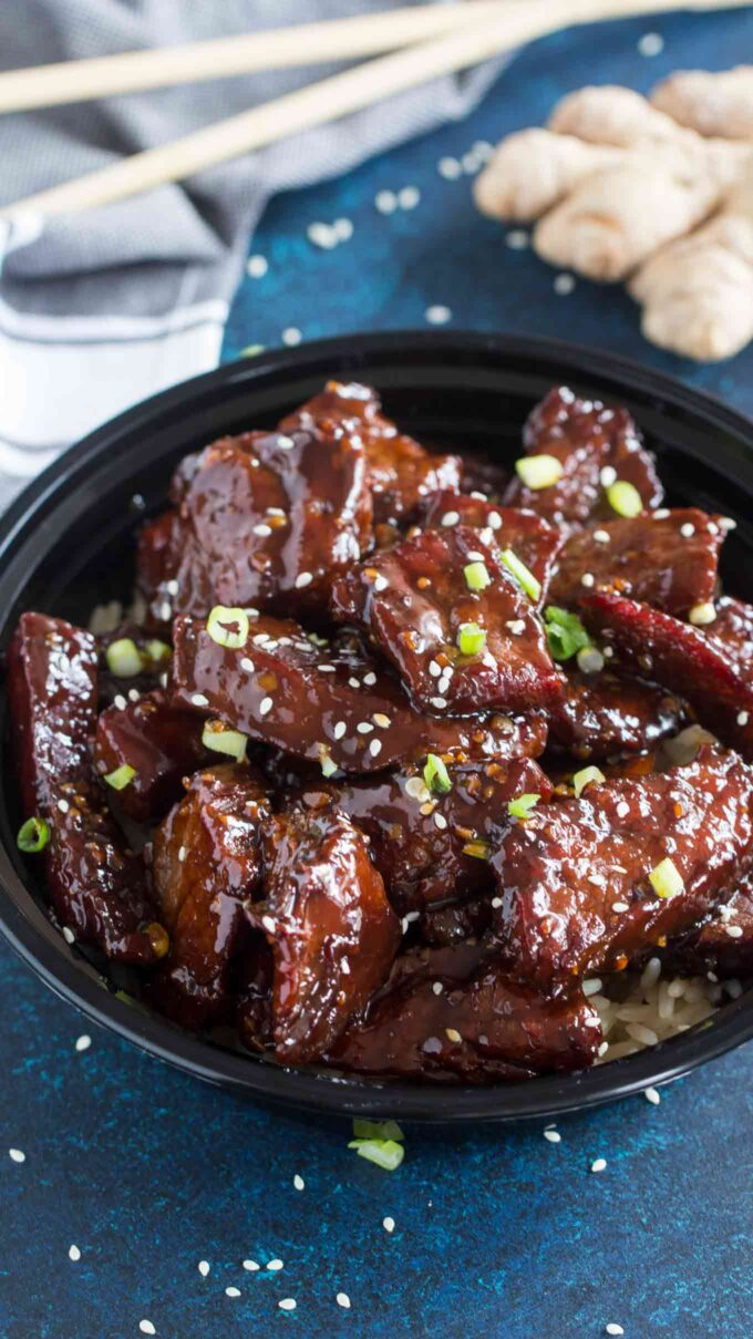 Photo of sticky honey garlic beef garnished with chopped green onions and sesame seeds.