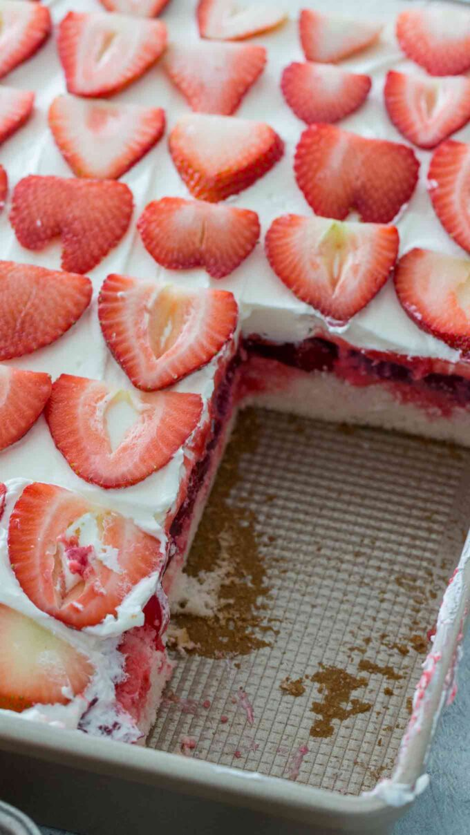 Strawberry cake topped with sliced strawberries on a baking pan