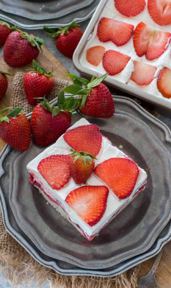 Homemade strawberry poke cake topped with strawberry pie filling and sliced strawberries