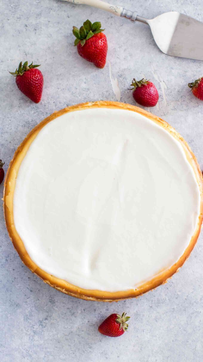 Baked classic cheesecake on a table with strawberries