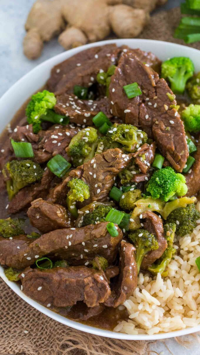 Image of instant pot beef and broccoli garnished with sesame seeds and rice on a white plate.