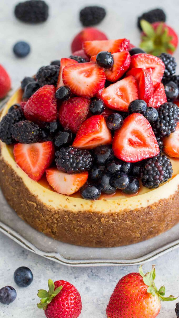 Image of instant pot cheesecake topped with strawberries and blackberries.