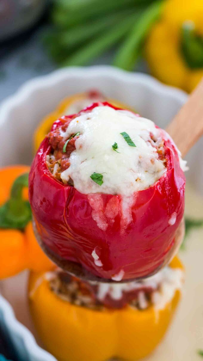 picture of instant pot stuffed pepper with beef and rice topped with melted cheese and chopped parsley on a wooden spoon