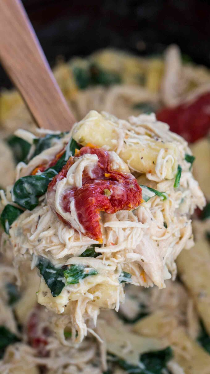 Crockpot Tuscan pasta with shredded chicken and cheese on a wooden spoon