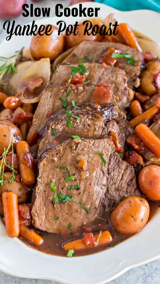 Image of Yankee pot roast with carrots and potatoes on a white plate.
