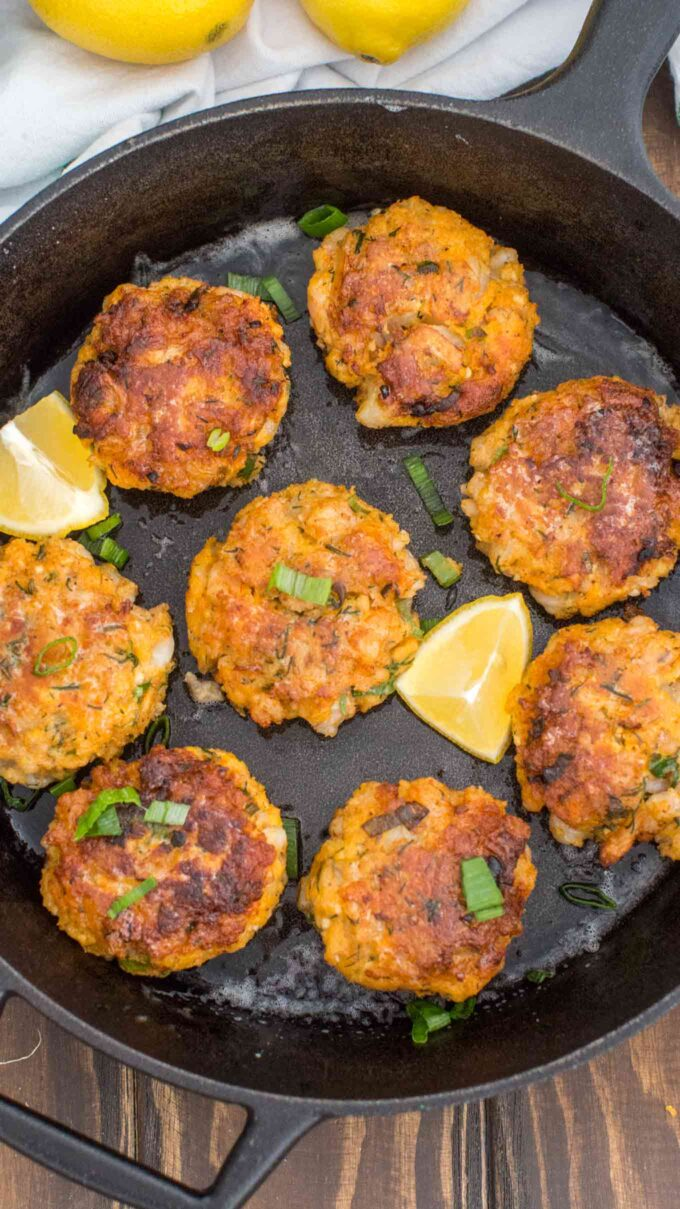 Picture of shrimp cakes in a skillet with sliced lemon.
