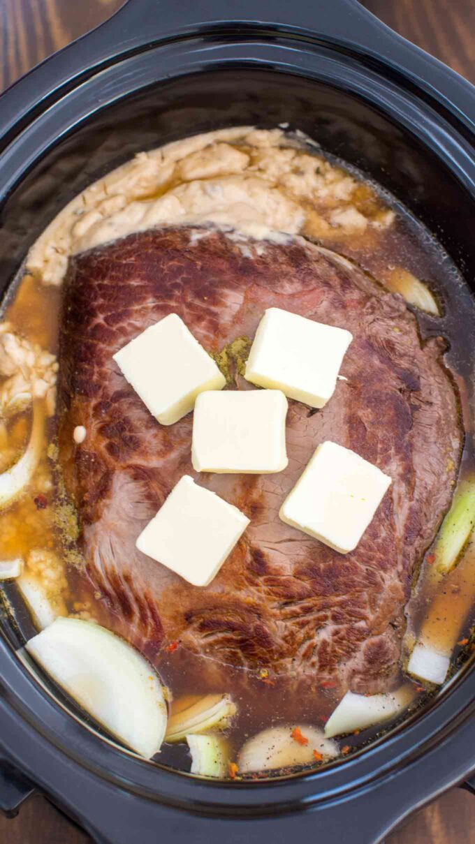 Picture of London broil beef cut in the crockpot topped with butter.
