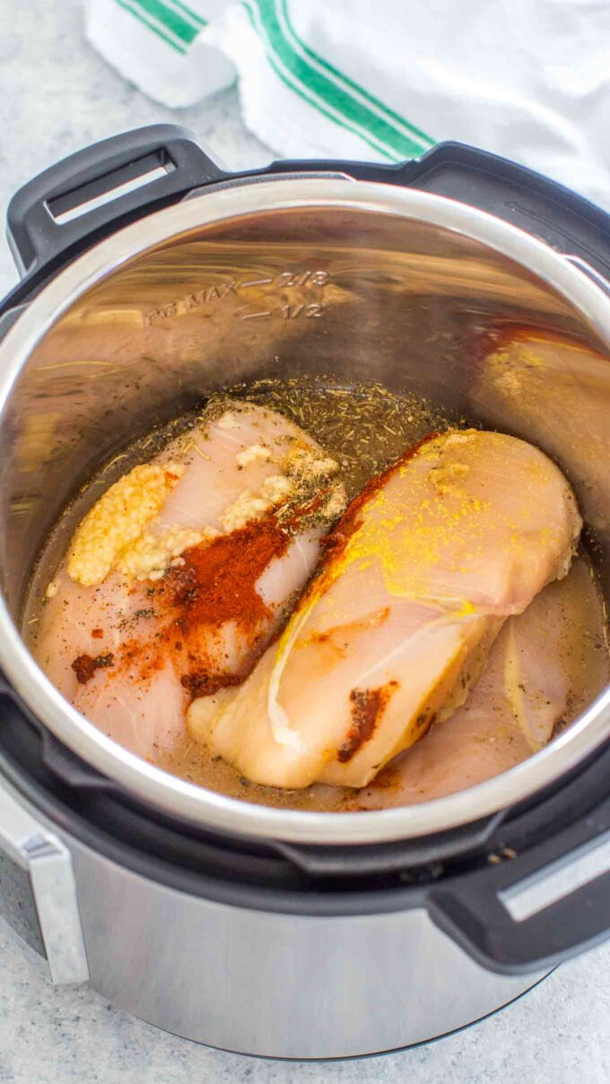 Photo of chicken breasts and spices in the instant pot.