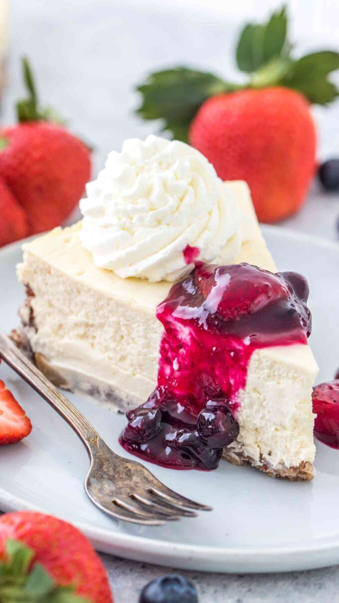Image of a slice of keto cheesecake with whipped cream.