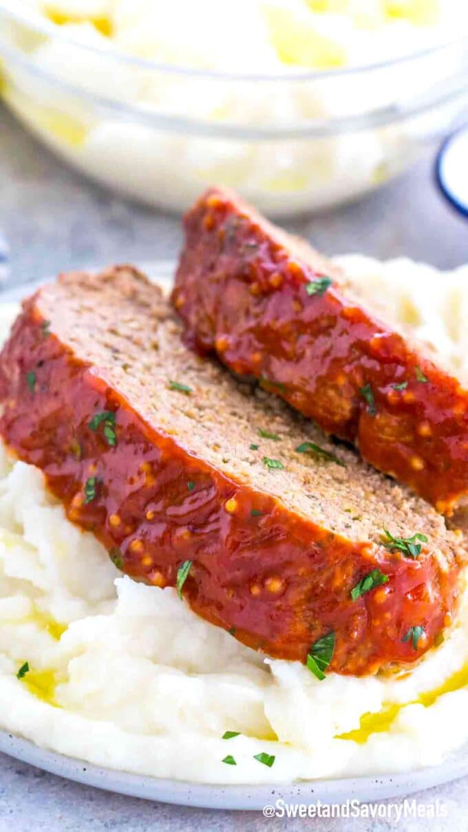 two homemade meatloaf slices on top of a plate with mashed potatoes