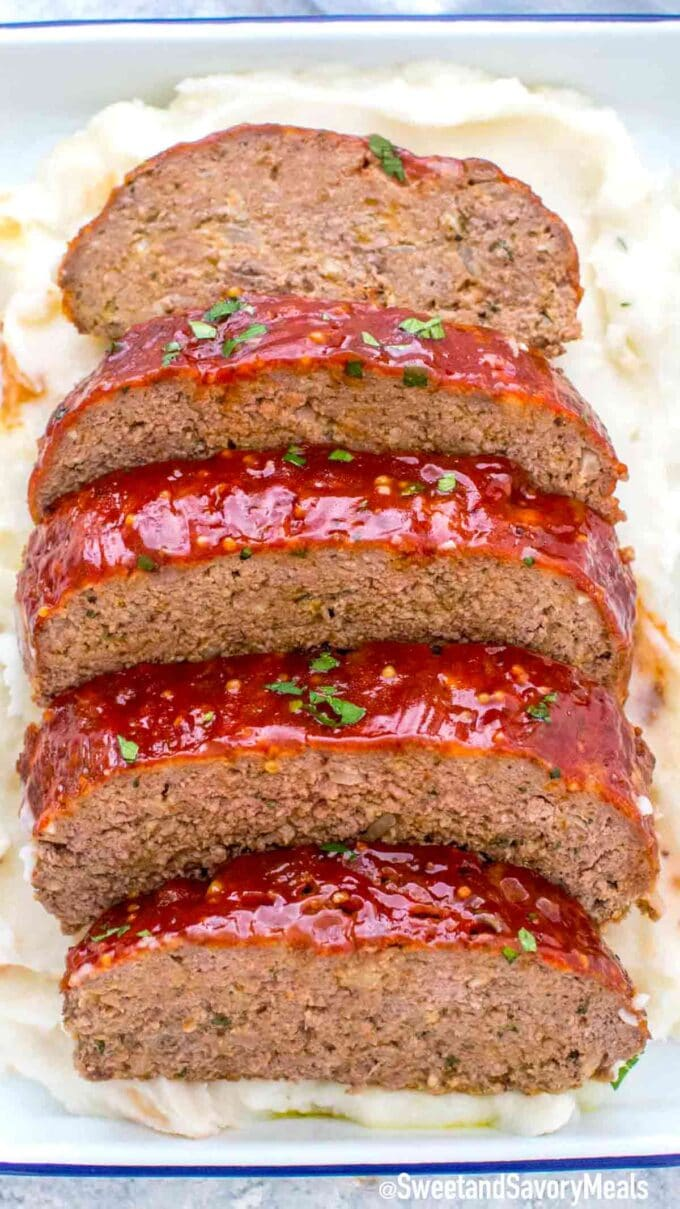 beef meatloaf in a tray on top of mashed potatoes
