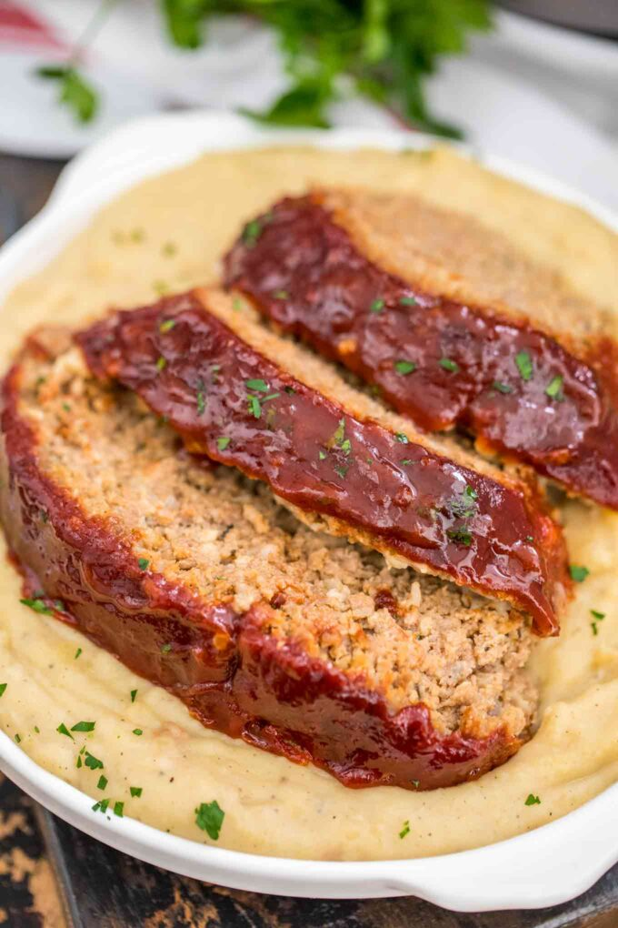 Image of instant pot meatloaf over mashed potatoes.