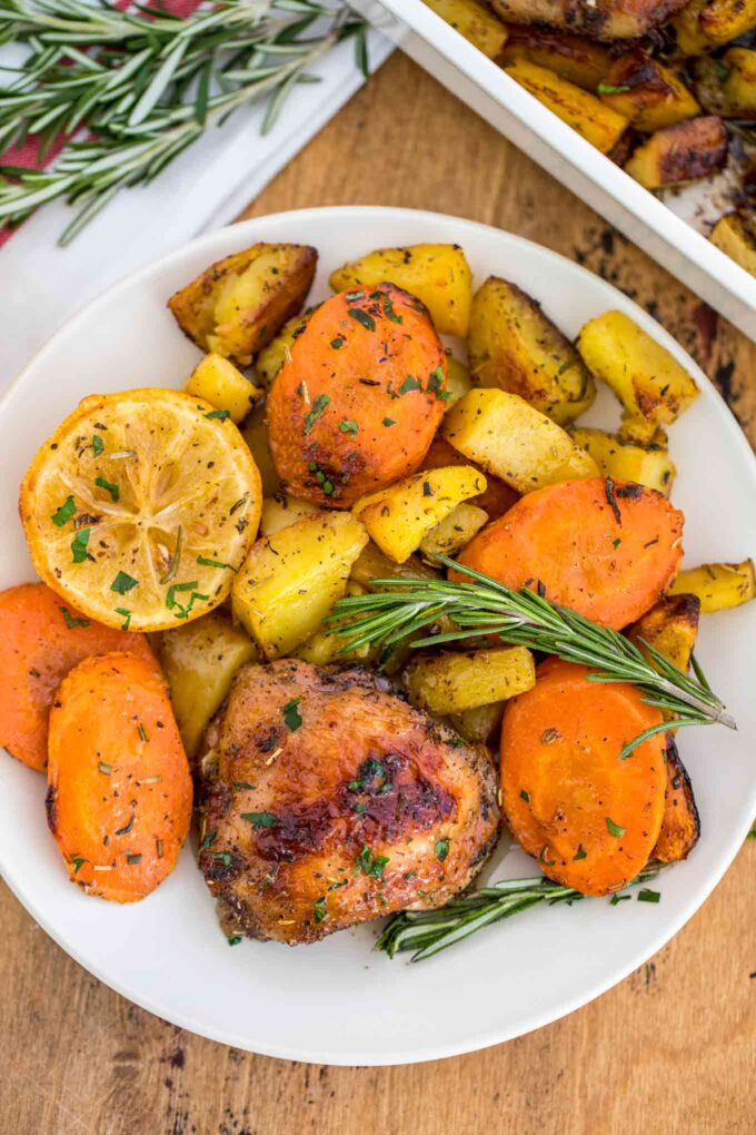 Picture of homemade Italian chicken and potatoes garnished with herbs and lemon.