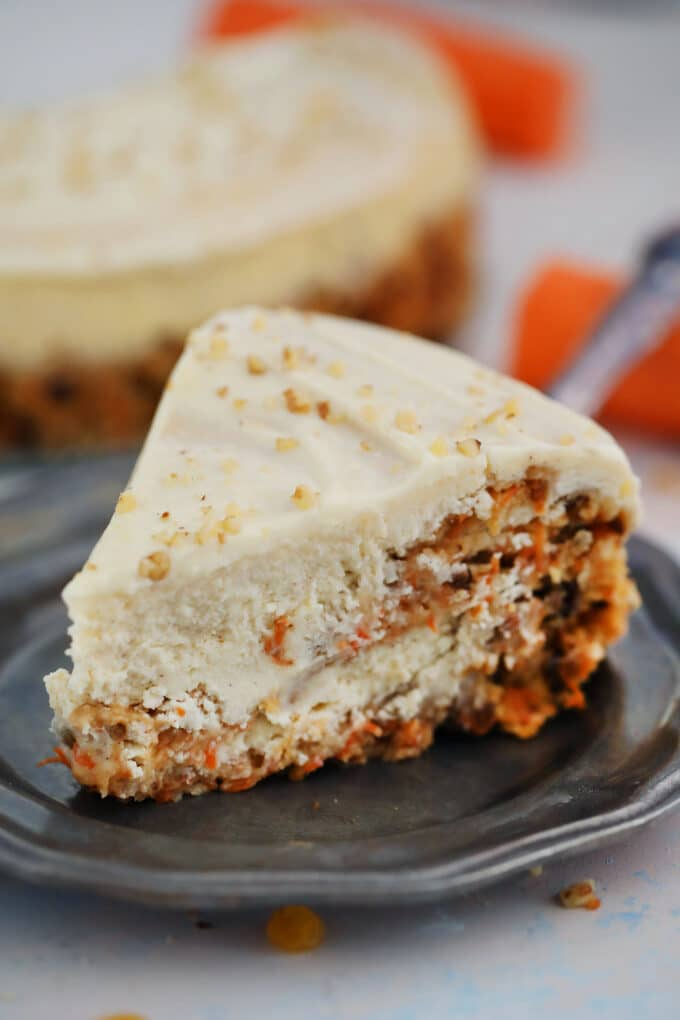 A slice of carrot cake cheesecake on a silver plate