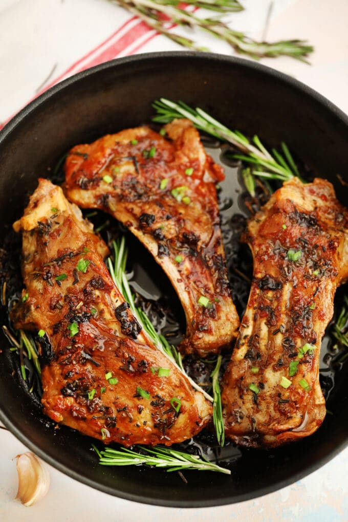 Image of cooked lamb ribs with herbs and rosemary.