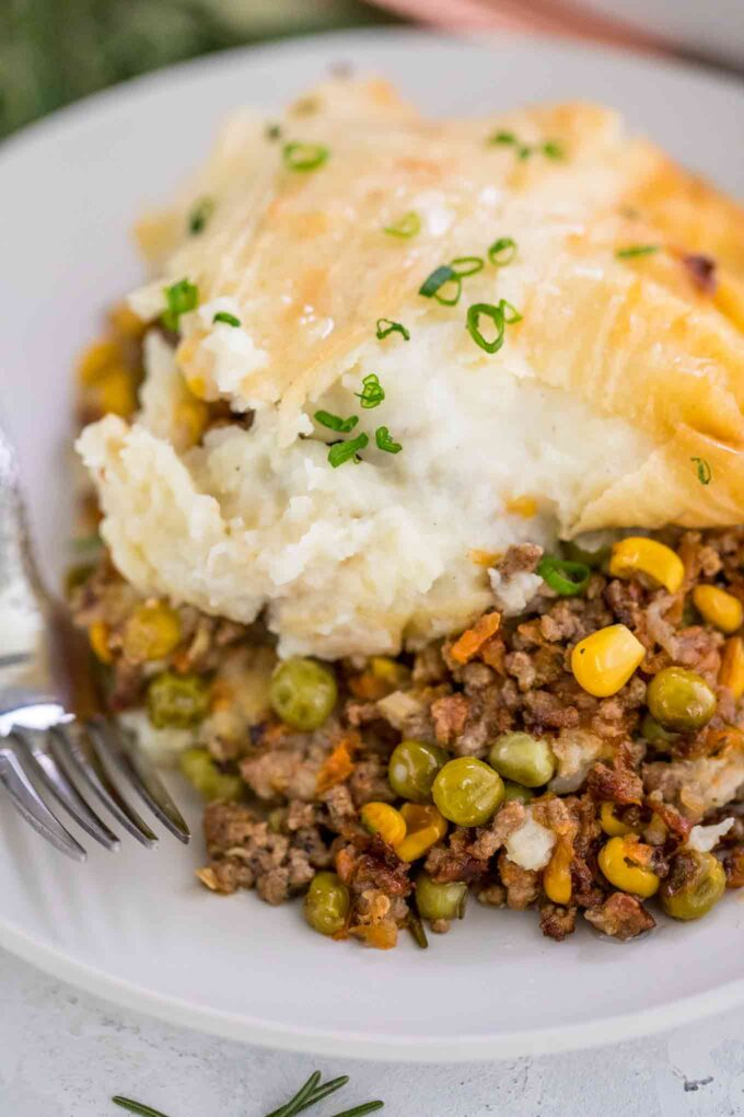 Picture of a sliced shepherd's pie on a white plate.
