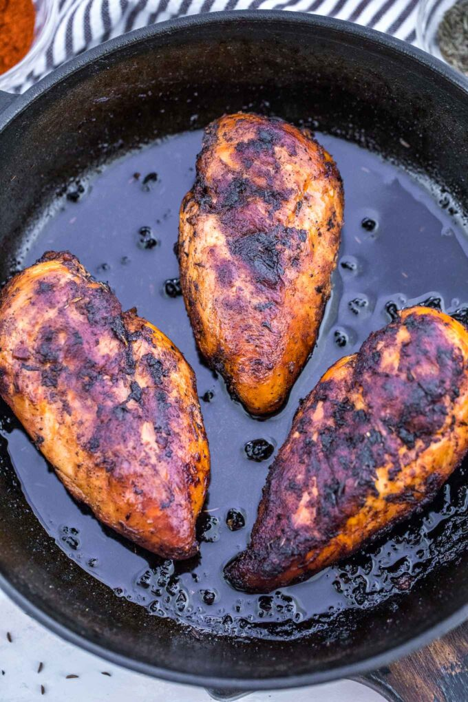 Image of blackened chicken breasts in a skillet.