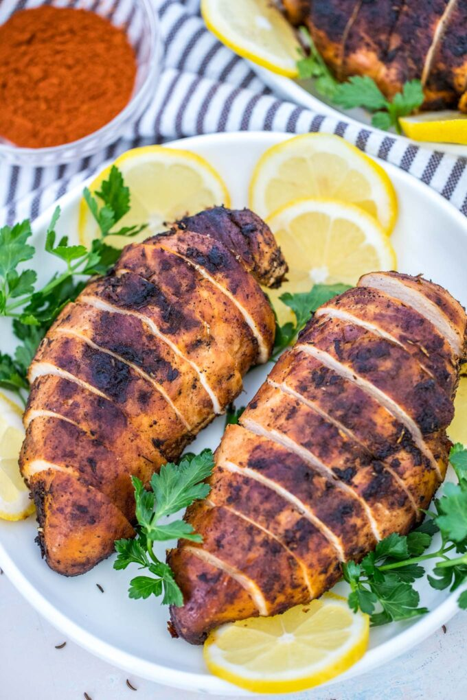 Picture of blackened chicken breasts with sliced lemon on a plate.