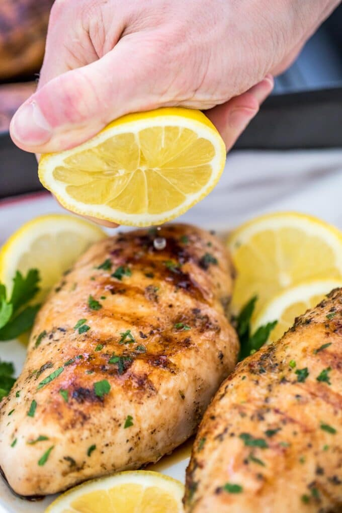 Image of grilled chicken breasts with lemon and chopped parsley.