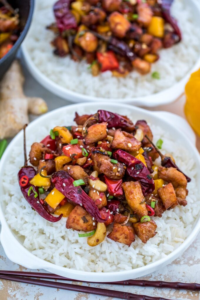 Photo of szechuan chicken over white rice in bowls.