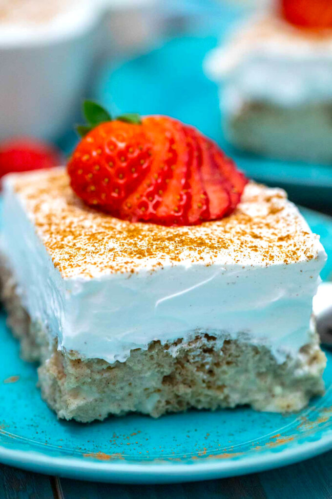 Image of authentic tres leches cake with whipped cream cinnamon strawberries.