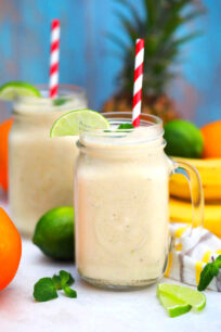 Photo of tropical smoothie with mango bananas pineapple and lime.