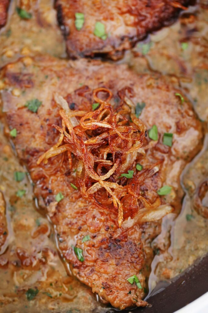 Photo of cube steak topped with caramelized onion and gravy.