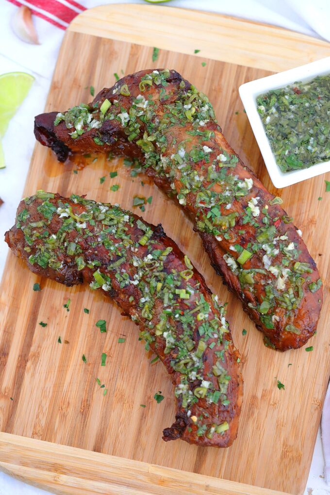 Photo of grilled pork tenderloin coated with soy sauce and chopped green onions.