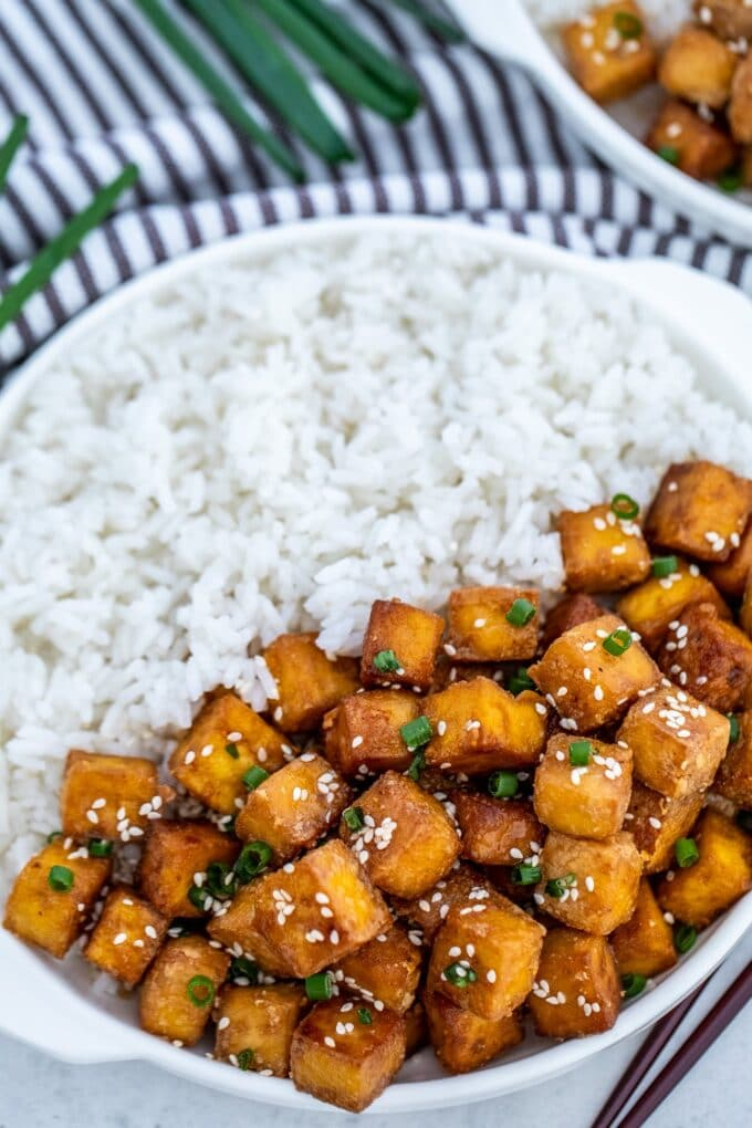 Image of baked tofu over white rice in a plate.