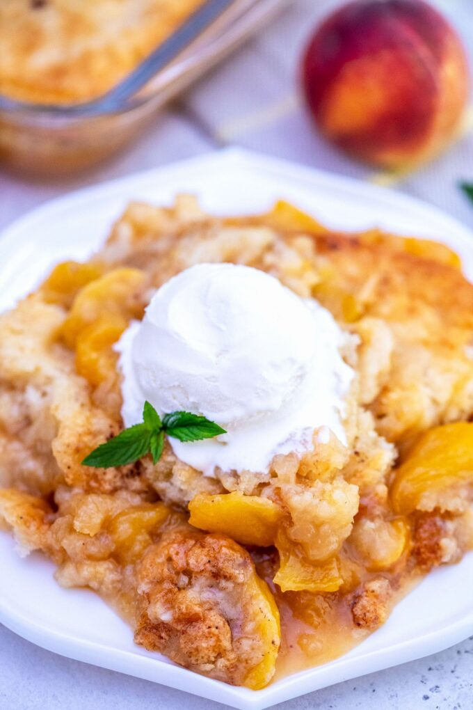 Image of peach cobbler topped with ice cream.