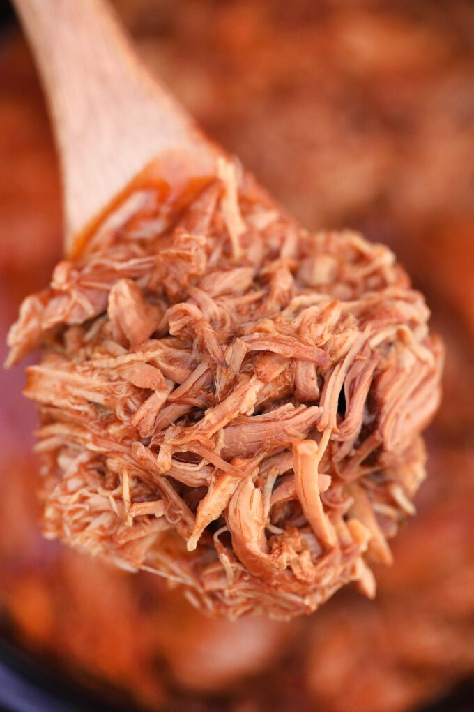 Shredded pulled pork cooked in the slow cooker with bbq sauce on a wooden spoon