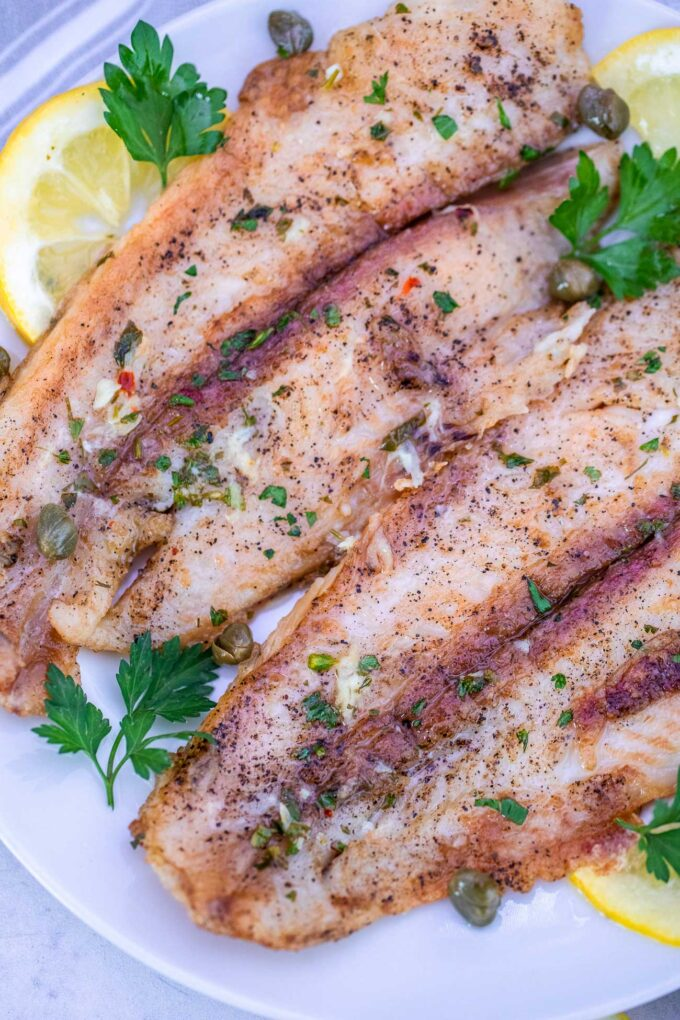 Swai fish garnished with lemon and chopped parsley photo.
